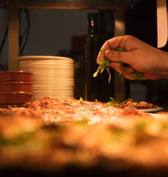 Someone preparing a pizza in Peatzeria restaurant on Islay